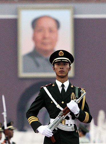 A paramilitary policeman stands guard in front of a portrait of the late chairman Mao Zedong on Tiananmen Square in Beijing