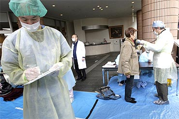 Medical staff screen people at a public welfare centre in Niigata, northern Japan
