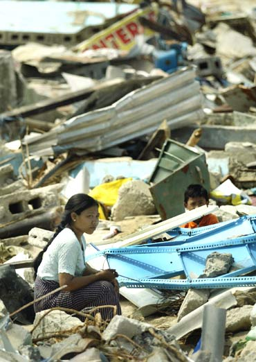 A Nicobarese family, who survived lthe Indian Ocean tsunami, sit among the debris of damaged houses in Lapathy village in the badly devastated Car Nicobar island in January 2005