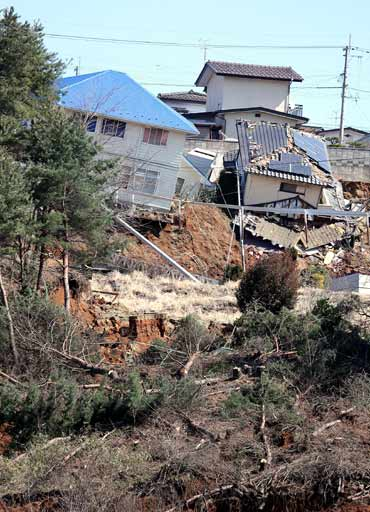 Houses are left damaged by landslides triggered by a quake off the coast of north-eastern Japan