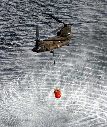 A Japan Air Self-Defense Force CH-47 Chinook helicopter collects water from the ocean to drop on the reactors at the Fukushima Daiichi nuclear plant