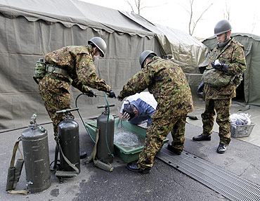 A man who was evacuated from the vicinity of Fukushima's nuclear power plant washes his head at Japan Ground Self-Defense Forces makeshift facility to cleanse people who might have been exposed to radiation
