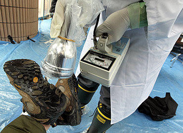 Medical staff screen the boots of a person who is concerned over radiation exposure at a public welfare center in Niigata, northern Japan