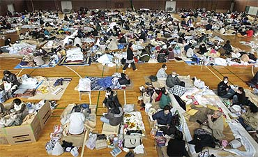 Evacuees, who fled from the vicinity of Fukushima nuclear power plant, sleep at an evacuation center