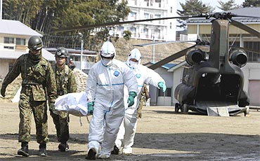 Japan Self-Defense Forces officers carry a victim who is suspected of being exposed to radiation