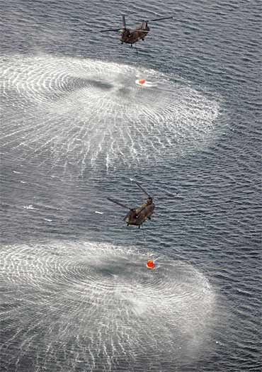 Japan Air Self-Defence Force helicopters collect water from the ocean to drop on the reactor