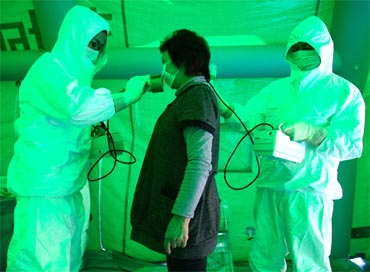 Medical staff use a Geiger counter to screen a woman for possible radiation exposure