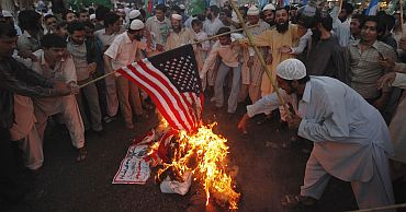 Supporters of Pakistan's religious and political party Jamaat-e-Islami set ablaze a US flag as they take part in a protest rally against the release Raymond Davis in Karachi