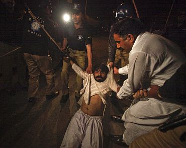 Police arrest an activist of a Pakistani political party during a protest rally in Lahore