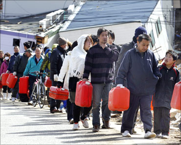 People queue up to buy gasoline at a village destroyed by the earthquake and tsunami in Ofunato, Iwate Prefecture