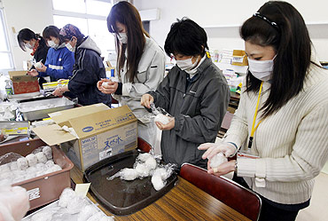 Volunteers make rice balls for survivors at a shelter in a village destroyed by the earthquake and tsunami