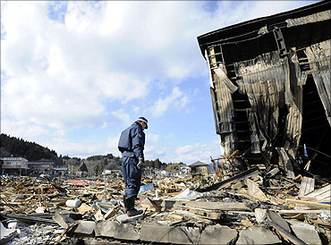 A police officer stands at an area destroyed by an earthquake and a tsunami in Kesennuma city, Miyagi Prefecture