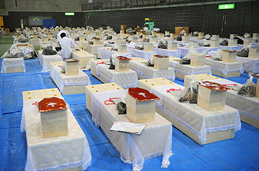 Caskets containing the bodies of earthquake and tsunami victims are arranged in a hall in Rifu-cho, Miyagi prefecture
