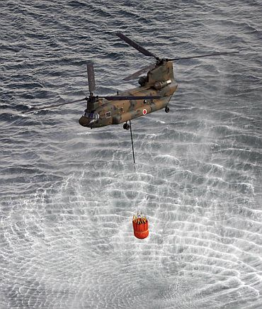A helicopter collects water from the ocean to drop on reactors at the Fukushima nuclear plant