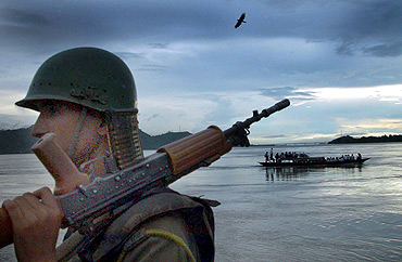 A soldier stands guard on the banks of the river Brahmaputra on the outskirts of Guwahati