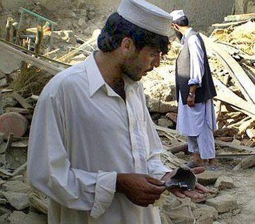 Pakistani villagers pick up rocket fragments after a drone strike