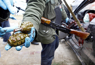 A rebel shows hand grenades found on fighters loyal to Gaddafi