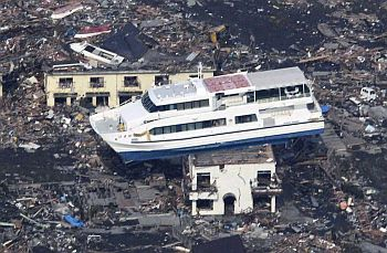 A ferry is perched on top of a house in the aftermath of an earthquake and tsunami in Otsuchi, Iwate prefecture