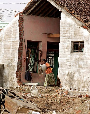 An tsunami survivor throws debris out of her damaged house in Nagappattinam, Tamil Nadu in January 2005
