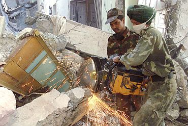 Indian soldiers use a concrete cutter at a collapsed apartment building in the western Indian town of Bhuj, where over 30,000 people died in the 2001 quake