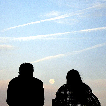 The moon rises over the skyline of New York as people stand along Hudson River in Hoboken, New Jersey
