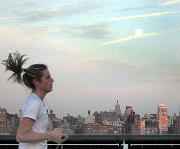 The moon rises over the skyline of New York as a jogger runs along Hudson River in Hoboken, New Jersey