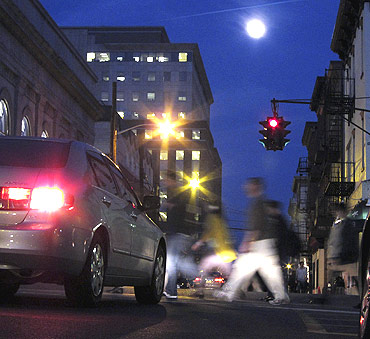 The moon rises as people cross a street in Hoboken, New Jersey