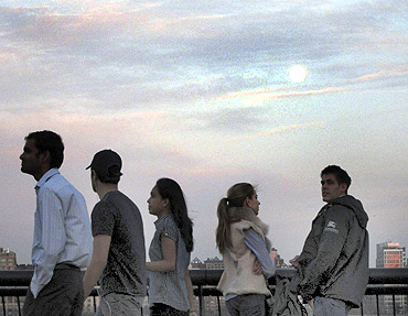 The moon rises over the skyline of New York as people stand along the Hudson River in Hoboken, New Jersey