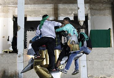 Supporters of Libya's leader Muammar Gaddafi form a human shield at his fortified compound in Tripoli on Saturday