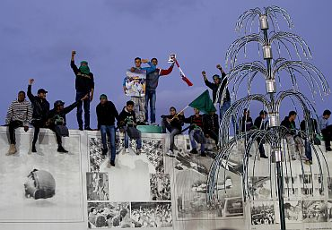 Youths standing on a wall of the house of Libya's leader Muammar Gaddafi form a human shield in Tripoli