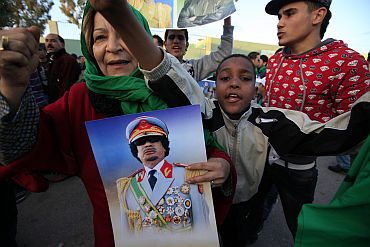 Supporters of Libya's leader Muammar Gaddafi shout slogans as they arrive at Bab Al- Aziziyah