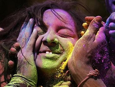 People apply coloured powder to a woman's face as they celebrate Holi
