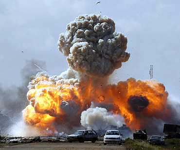 Vehicles belonging to forces loyal to Gaddafi explode after an air strike by coalition forces, along a road between Benghazi and Ajdabiyah