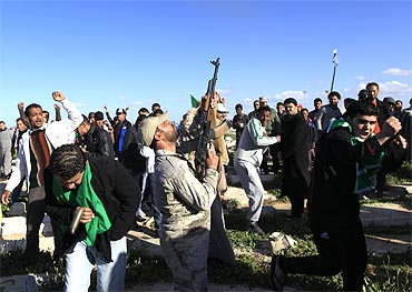 A Libyan soldier fires in the air during the funeral of persons who were killed by US air strikes