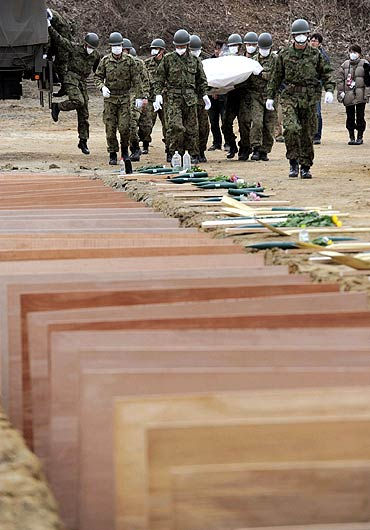 Japan Ground Self Defense Force members prepare to bury victims of the March 11 earthquake and tsunami at a temporary mass grave in Higashi Matsushima, northern Japan