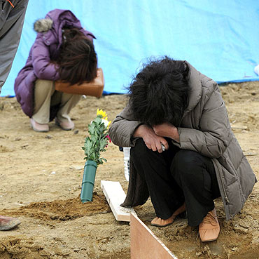 Relatives mourn the victims of the Japan disaster at a mass grave