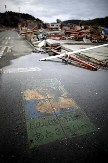 A tsunami refuge warning painted on the road is seen in an area destroyed by the earthquake
