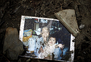 A family picture is seen at the remains of a house after the earthquake and tsunami in Minamisanriku