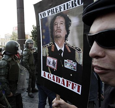 A demonstrator holds a poster with the picture of Libya's leader Muammar Gaddafi is front of riot policemen during a protest against the visit by US President Barack Obama, in Santiago