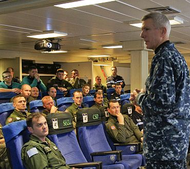 Adm Samuel J Locklear, III, commander, Joint Task Force Odyssey Dawn, speaks with an aircrew team from the French Navy aircraft carrier Charles de Gaulle