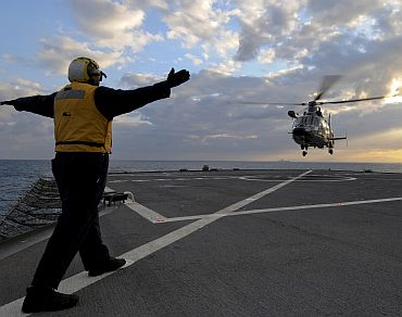 A French navy AS365 F Dauphin rescue helicopter from French aircraft carrier Charles de Gaulle test lands aboard the amphibious command ship USS Mount Whitney. Charles de Gaulle is operating in the Mediterranean Sea supporting the coalition led operations in response to the crisis in Libya