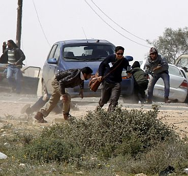 Foreign journalists take cover during an air strike at a rebel fighters checkpoint in Al Ugaila area along a road between the towns of Brega and Ras Lanuf