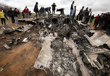 People look at a US Air Force F-15E fighter jet after it crashed near the eastern city of Benghazi