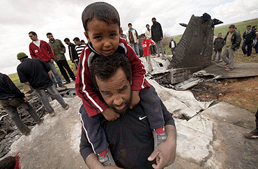 A man carries his son as they stand at a destroyed US Air Force F-15E fighter jet after it crashed