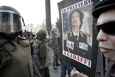A demonstrator holds a poster with the picture of Libya's leader Muammar Gaddafi