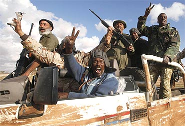 Rebels celebrate in a vehicle along the road near Benghazi