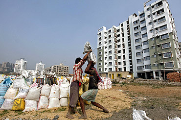 Labourers work at the site of a residential estate in Kolkata