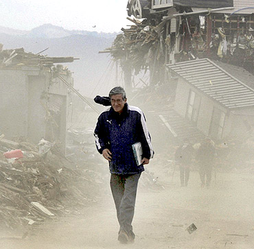 A man walks through rubble amidst dust blown up by wind in Rikusentakata, Japan