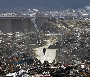 A survivor walks through debris in Rikuzentakata, Japan