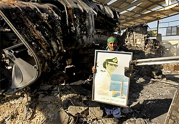 A Libyan holds a poster of Muammar Gaddafi at a naval military facility damaged by air strikes